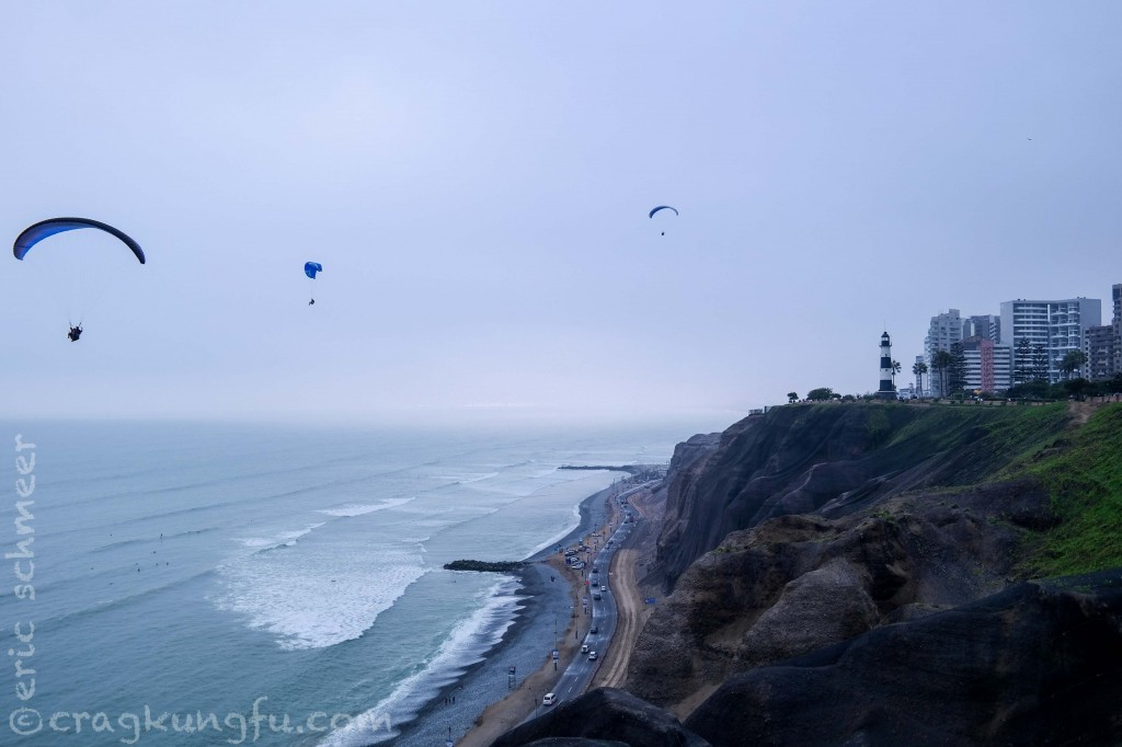 Paragliders and surfers play by the cliffs on the malecon