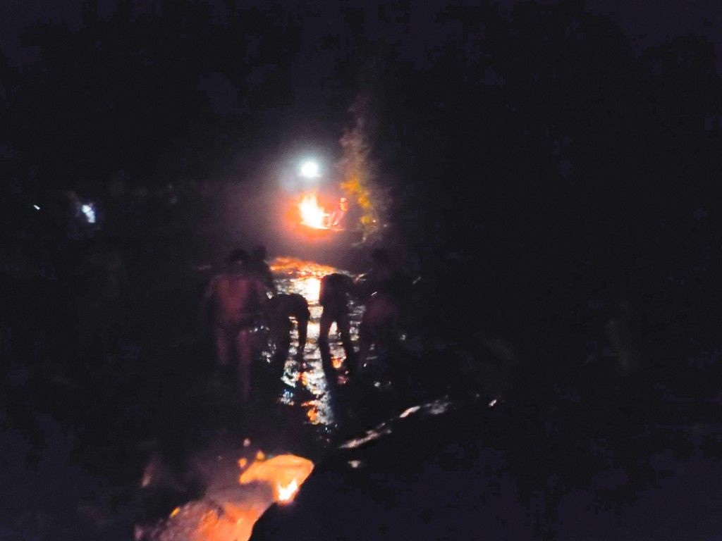 Locals cleansing in the cascada by firelight