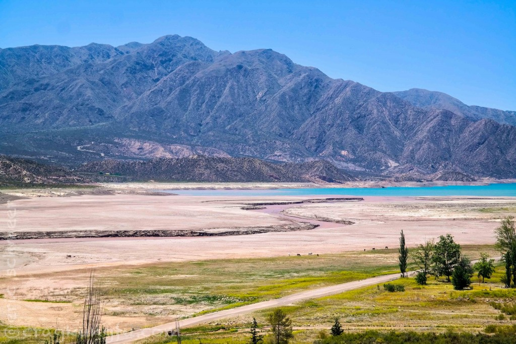 A muddy red river runs into the gorgeous blue waters of Embalse Potrerillos